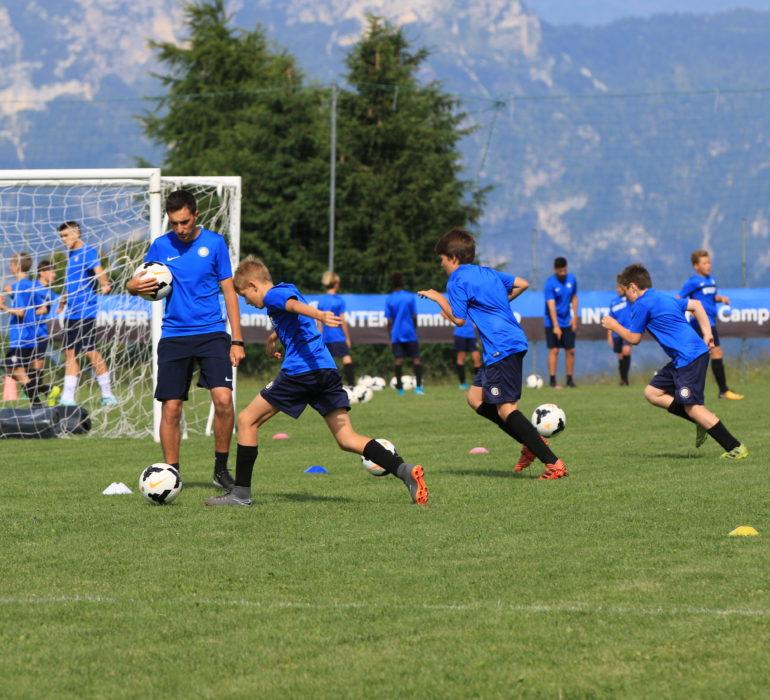 Istruttore dell'Inter Summer Camp supervisiona un calcio verso la porta